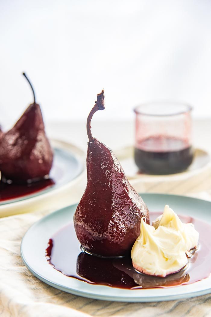 A single red wine poached pear on a blue plate with red wine syrup and mascarpone cheese on the side.