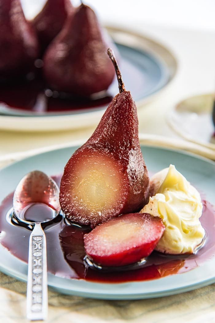 A single red wine poached pear on a blue plate with red wine syrup, with a piece cut off to show the middle, with a spoon on the side.