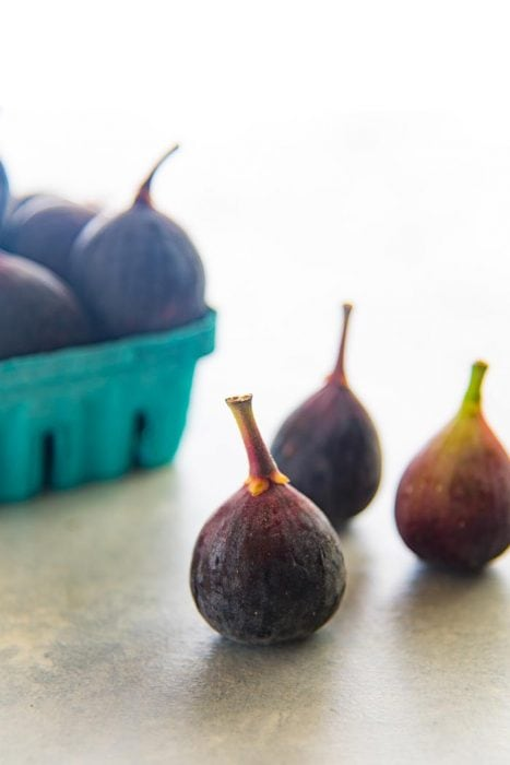 Three Black Mission Figs on a white table, with more black mission figs in a green punnet.
