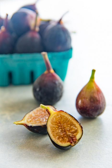 A black mission fig cut in half, with whole black mission figs in the background and in a punnet.