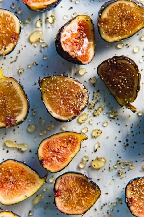 Halved black mission figs drizzled with honey, sherry and black pepper.