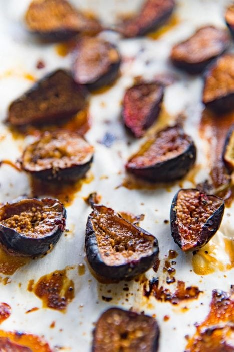 Roasted figs out of the oven, on a parchment paper lined baking tray.