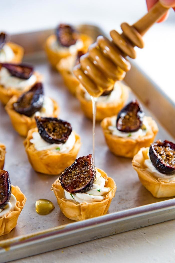 Roasted fig tartlets on a tray. Drizzling the roasted fig tartlet with extra honey.