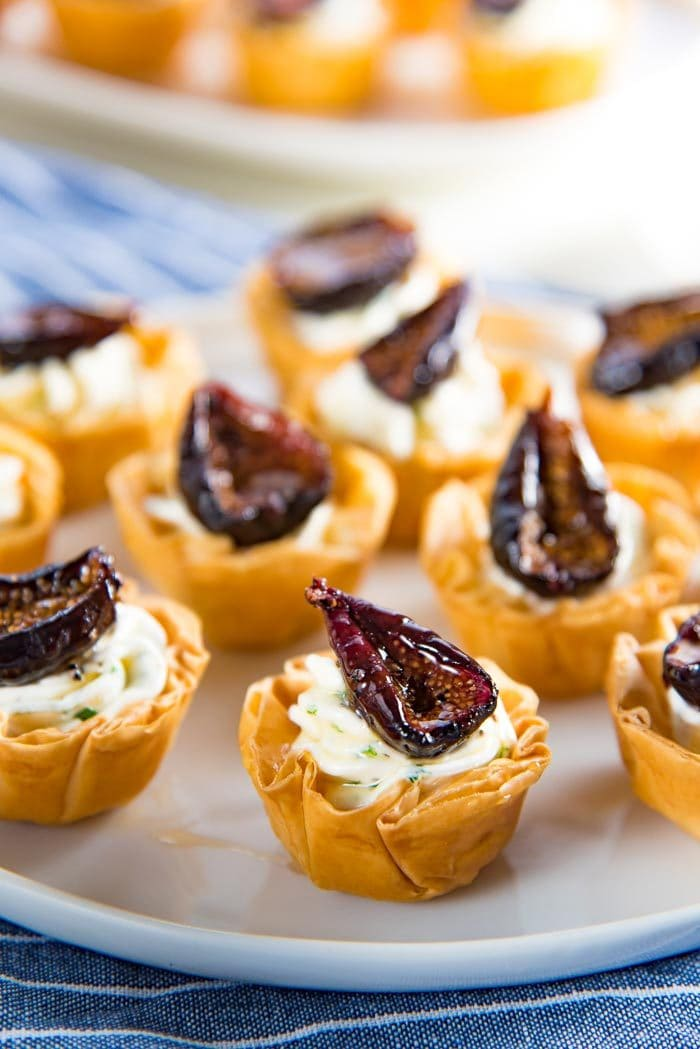 The goat cheese phyllo cup appetizers with figs on a white plate ready to be served.