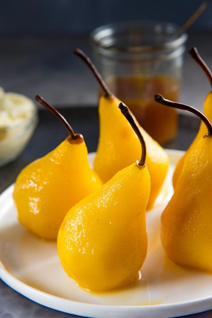 Five perfectly poached pears in saffron, cardamom and orange, on a white plate, on a dark tray with the saffron syrup and whipped mascarpone