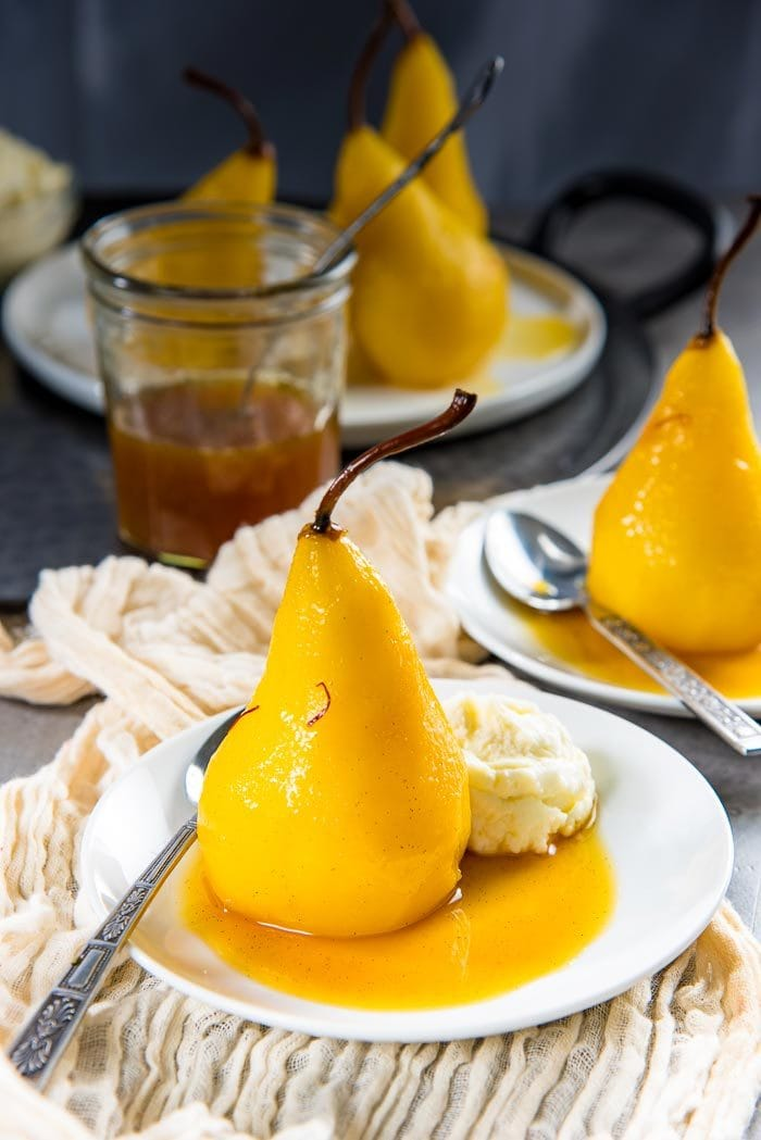 A cardamom saffron pear on a white plate, in the saffron syrup, with some whipped mascarpone on the side and a spoon. More poached pears in the background.