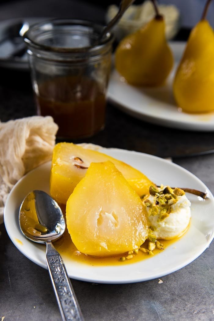 A saffron poached pear cut in half on a small white plate, placed on the saffron syrup. Whipped mascarpone cheese with chopped pistachios on the side.