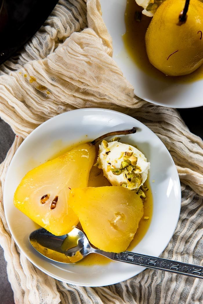 An overhead view of the saffron poached pears cut in half, served with whipped mascarpone and chopped pistachios.