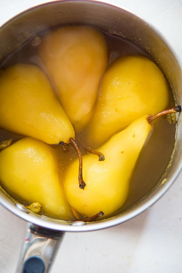 Saffron Poached Pears in a saucepan, after being poached and cooling down in the liquid.