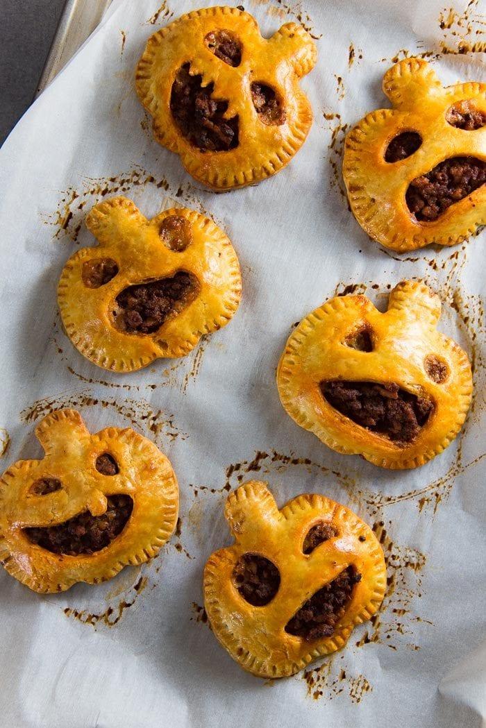 Baked Spooky chorizo hand pies, shaped like pumpkin heads.