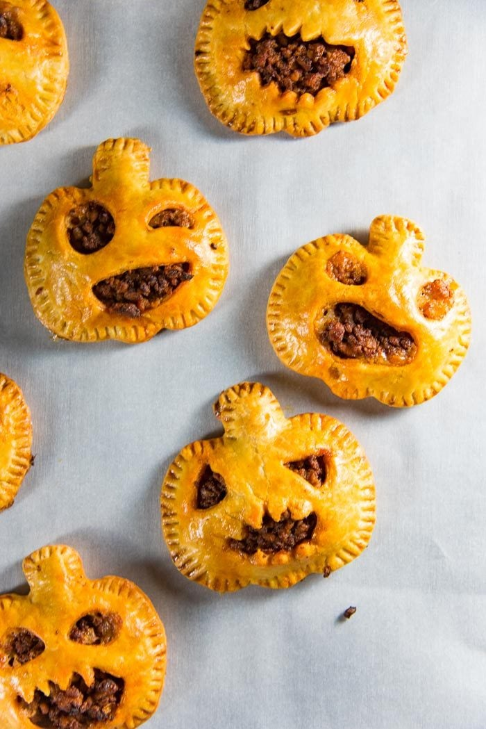 An overhead view of baked spooky chorizo hand pies, on parchment paper.