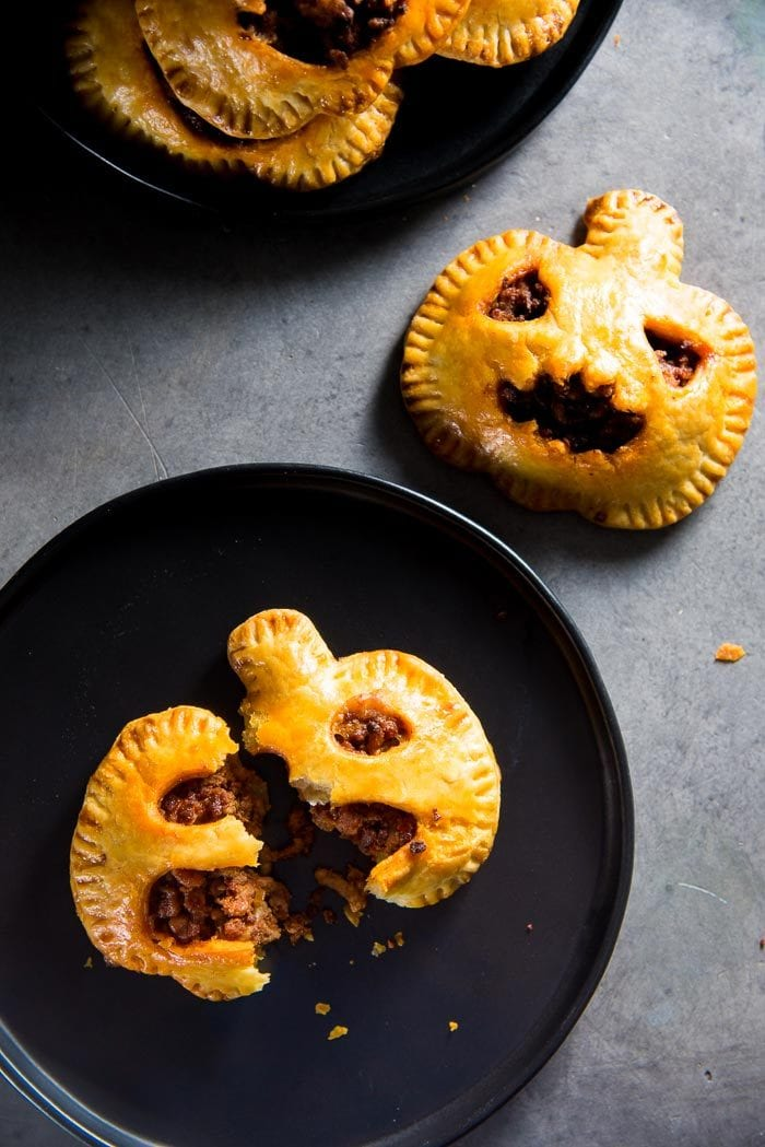 A chorizo hand pie shaped like a pumpkin on a black plate and split into two, with more pumpkin shaped hand pies on the grey table top.
