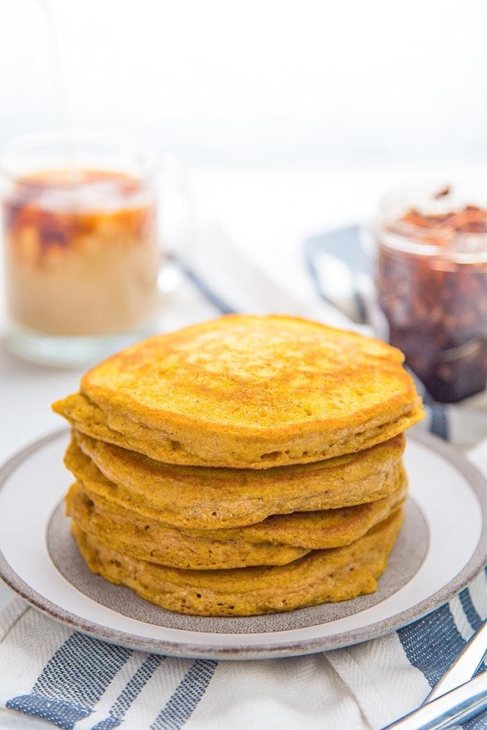 A stack of fluffy and easy pumpkin pancakes on a white and grey plate, with no toppings. A coffee mug and maple pecan topping in the background.