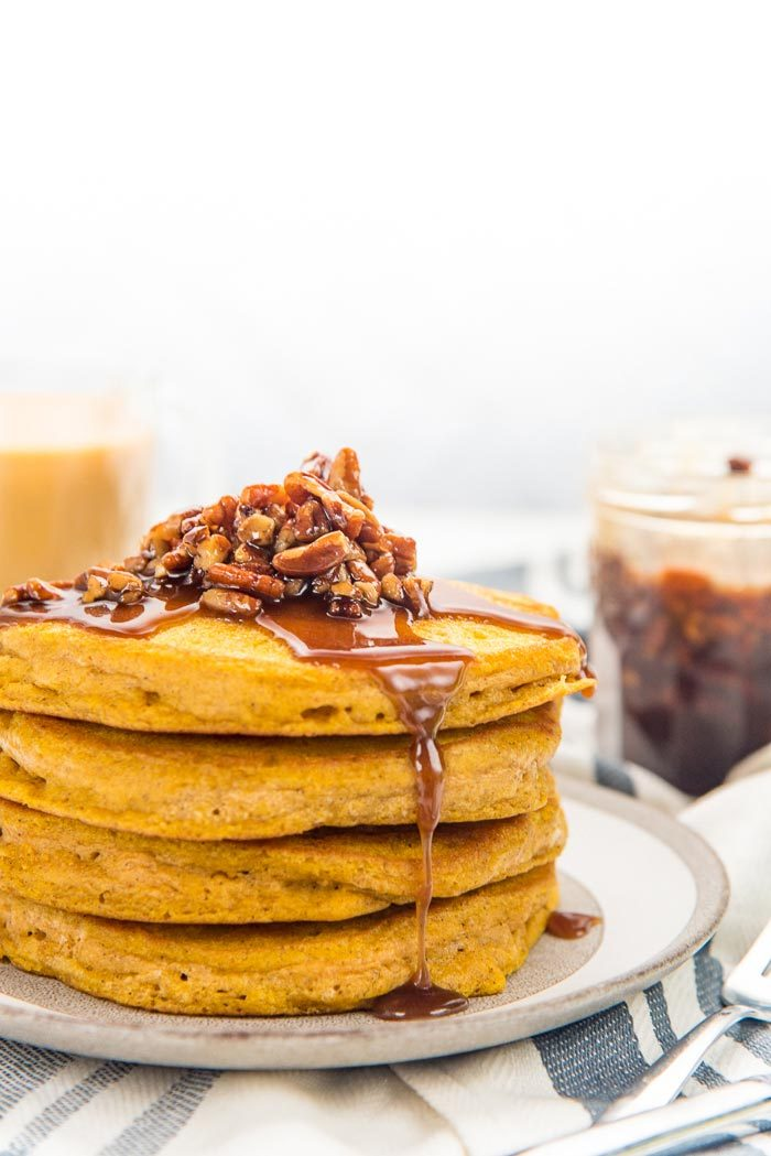 A close up of the stack of fluffy pumpkin pancakes, on a plate with maple pecan topping on top, and the syrup dripping down the front of the pancake stack.