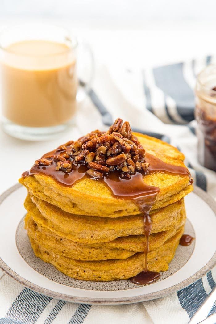 A stack of fluffy pumpkin pancakes, on a plate with maple pecan topping on top.