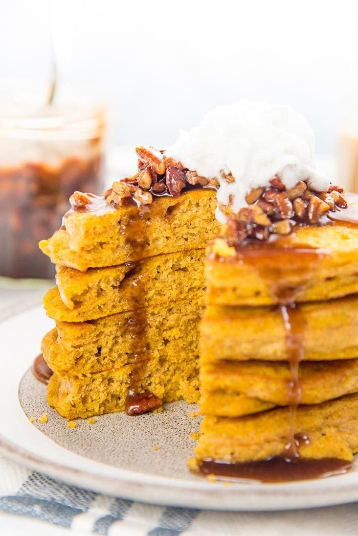 A side on view of a stack of fluffy pumpkin pancakes, with a wedge cut out, on a grey and white plate, with maple and pecan topping on top, with maple syrup drizzling down the pancakes.