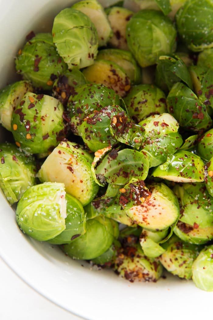 Halved Brussels sprouts in a white bowl, with chili flakes, salt and maple syrup added.