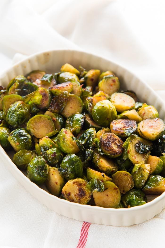 Maple roasted Brussels sprouts in a white oval dish, on a white table top.