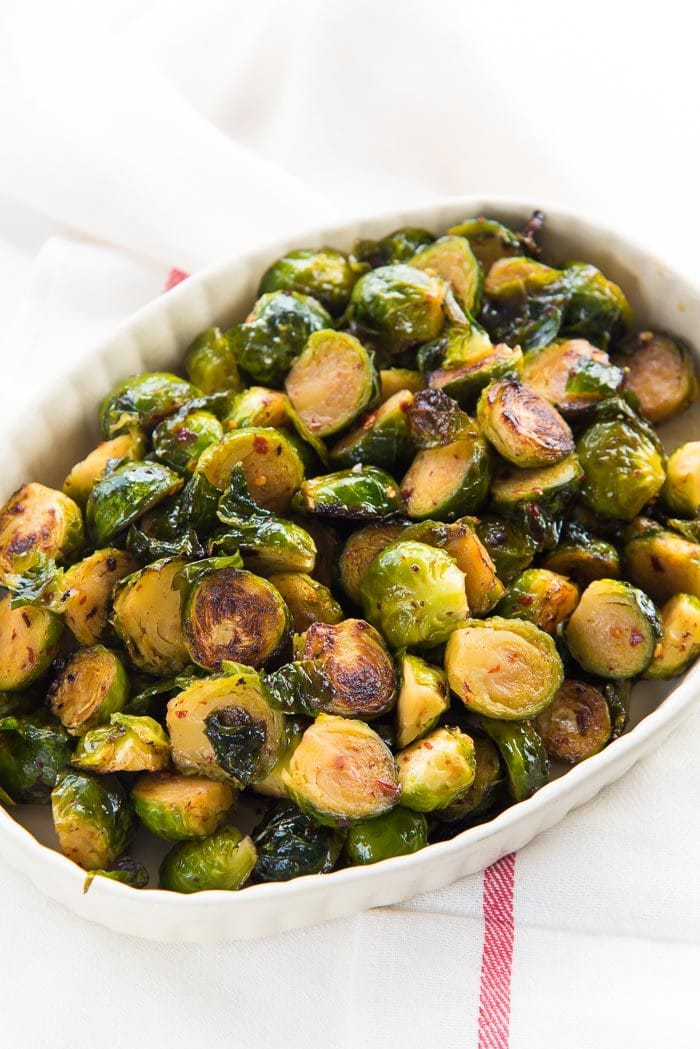 Maple Roasted Brussels Sprouts - A healthy, simple side dish for Thanksgiving, Christmas or any roast dinners. Deliciously crispy and caramelized with sweet and spicy flavors. Vegan and Paleo.