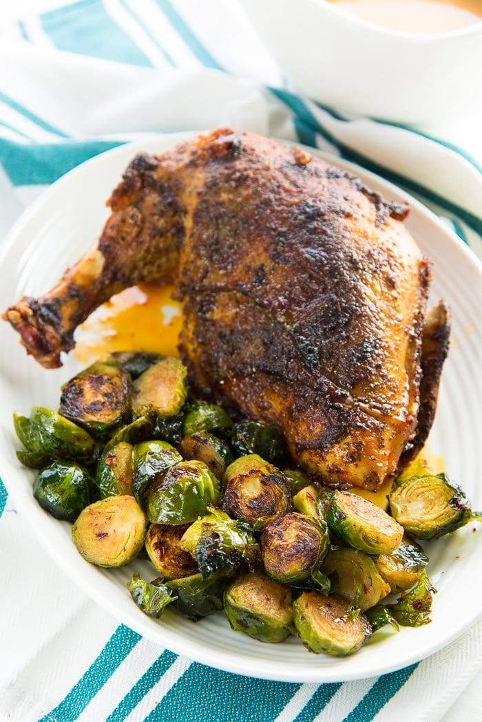 The maple roasted brussels sprouts are served as one of the Thanksgiving side dishes, alongside Roast Turkey, served on a white platter.