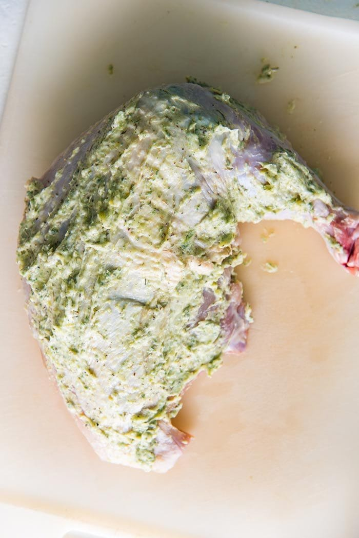 The sage garlic butter has been rubbed all over the turkey breast cut.