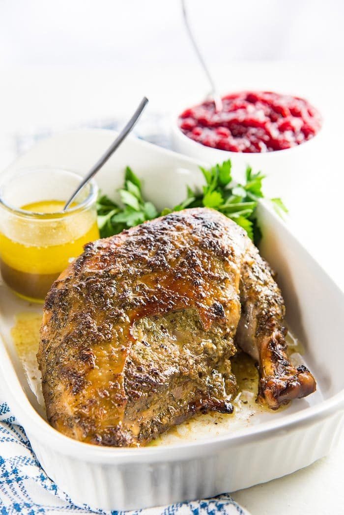 The slow cooker turkey breast roast on a white platter with pan drippings, served with cranberry sauce in a separate bowl in the background.
