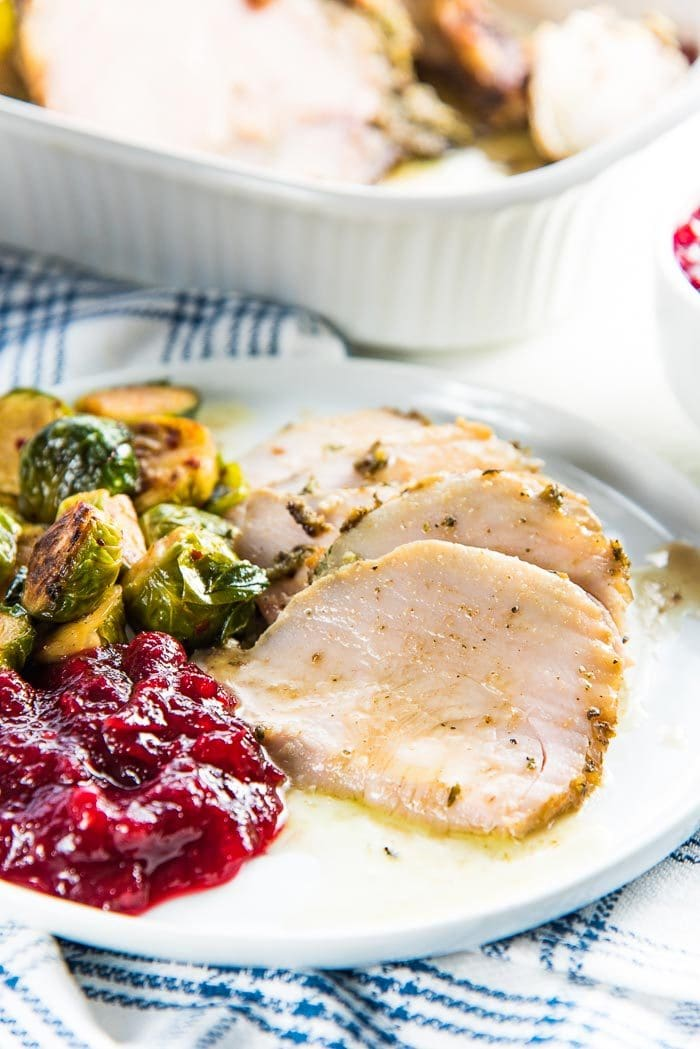 A close up of the slow cooker turkey breast slices, to show how juicy they are, with pan drippings poured over with ranberry sauce and brussels sprouts as side dishes.