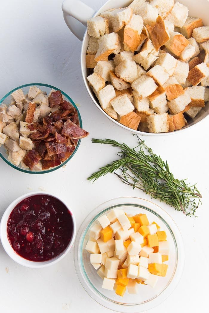 An overhead view of the Ingredients for the Thanksgiving leftover strata on a white table - Cranberry sauce, cubed cheese, leftover turkey, crispy bacon, herbs and dried or stale bread cubes.