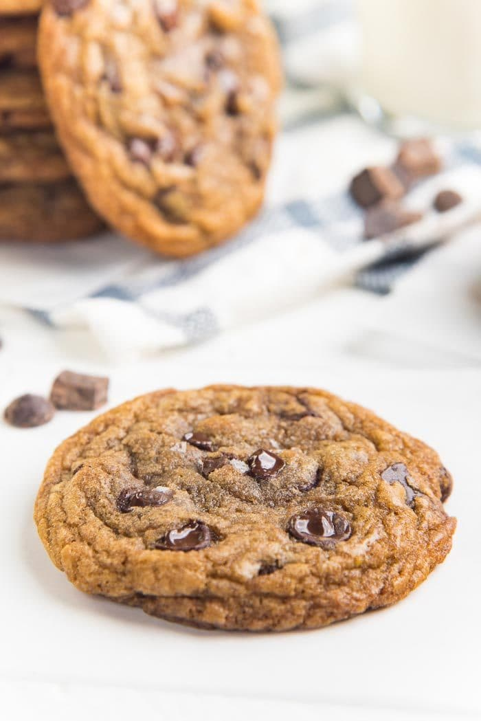 A close up of a single chocolate chip cookie with melted chocolate chip pockets on a white table top