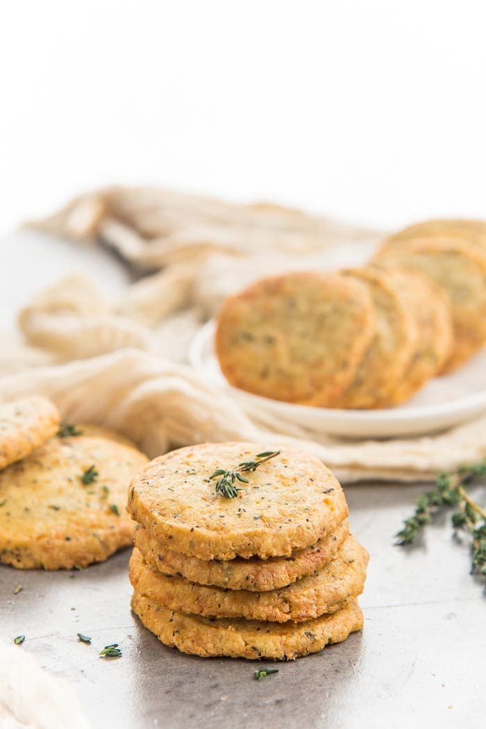 A stack of thyme and cheddar cheese cookies placed in the foreground with more cheddar cookies in the background on a white platter, with sprigs of thyme.