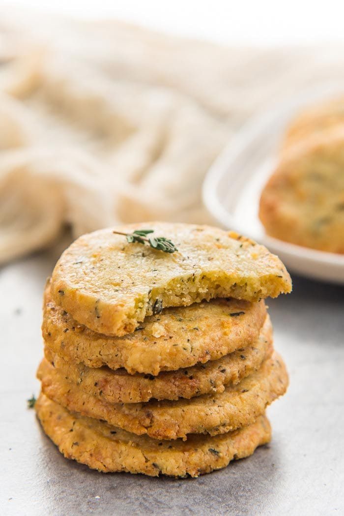 A stack of thyme and cheddar cheese cookies with 4 whole cookies and a bite taken out of the top cookie, with more cookies in the background.