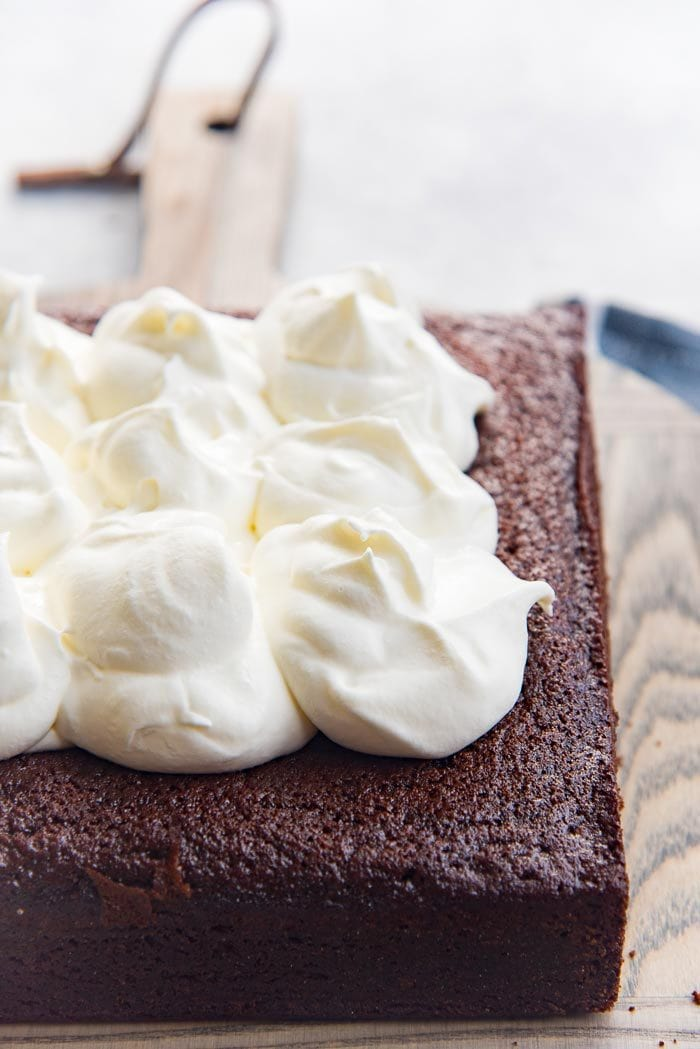 Generous dollops of whipped cream placed on top of the cheesecake stuffed gingerbread cake, placed on a wooden board.