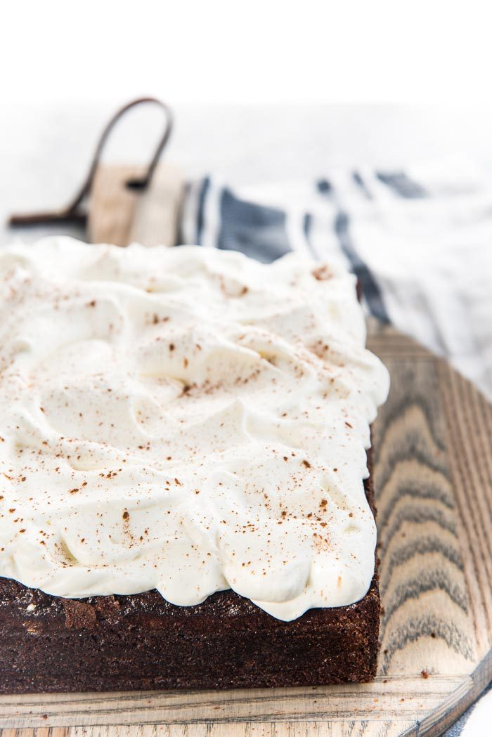 Whipped cream frosting swirled on top of the cheesecake stuffed gingerbread cake, with ground cinnamon sprinkled on top.