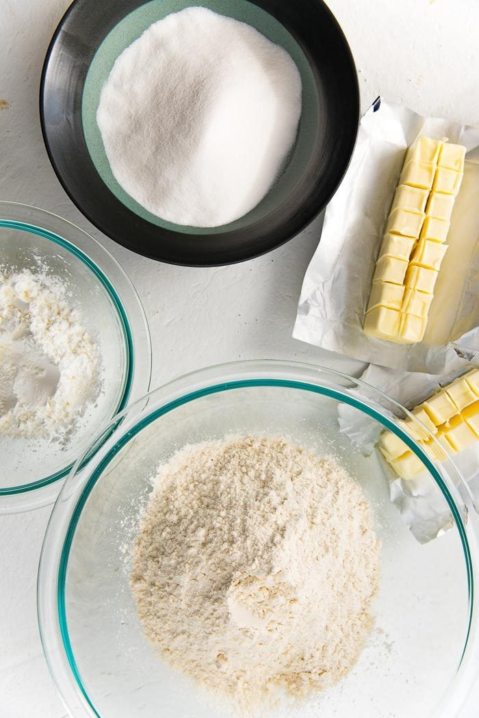 Overhead view of ingredients to make Shortbread Cookies, from butter, flour, rice flour and sugar in separate bowls.