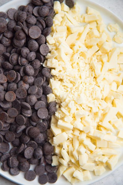 Both semi sweet chocolate and white chocolate on plate to be added to the cookie dough.