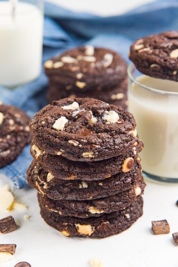 A stack of double or triple chocolate chip cookies on a white table.