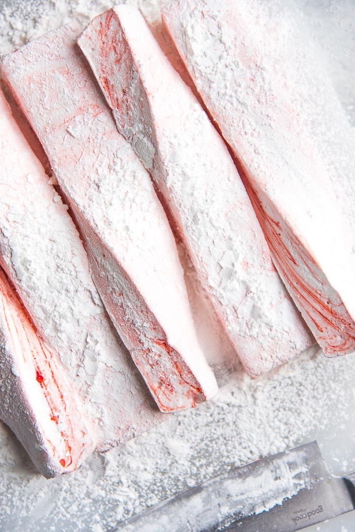 White and Red swirled peppermint marshmallows cut into strips on a white cutting board with mallow dusting powder.