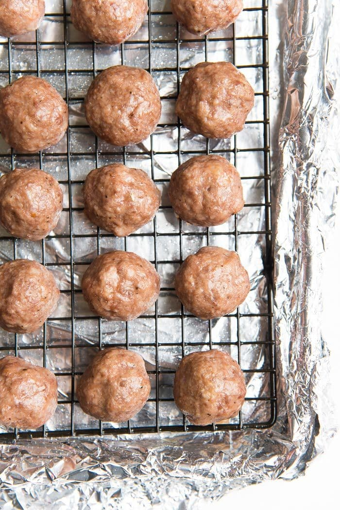 Homemade baked meatballs that are juicy and easy to make, on a wire rack over a half sheet pan.