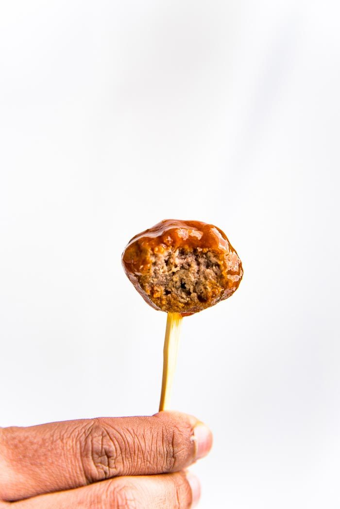 A cocktail meatball with a bite taken out, being held up.