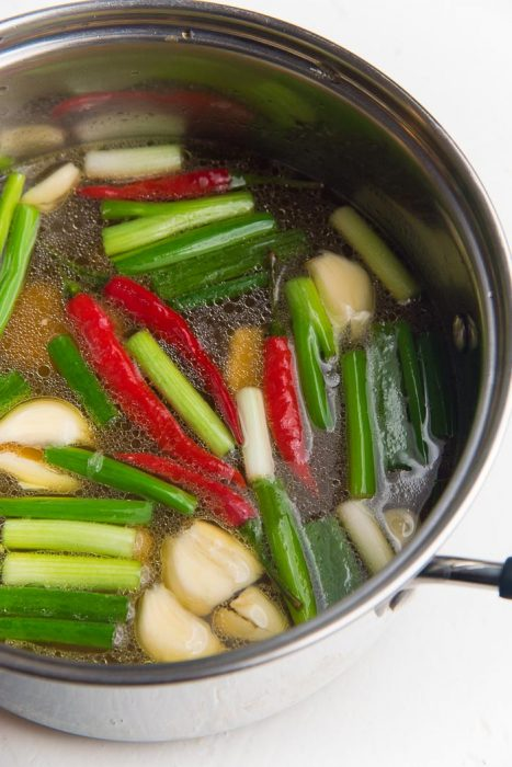 Process of making the chicken ramen broth - Chicken stock in a saucepan with garlic, ginger, spring onions and chili.