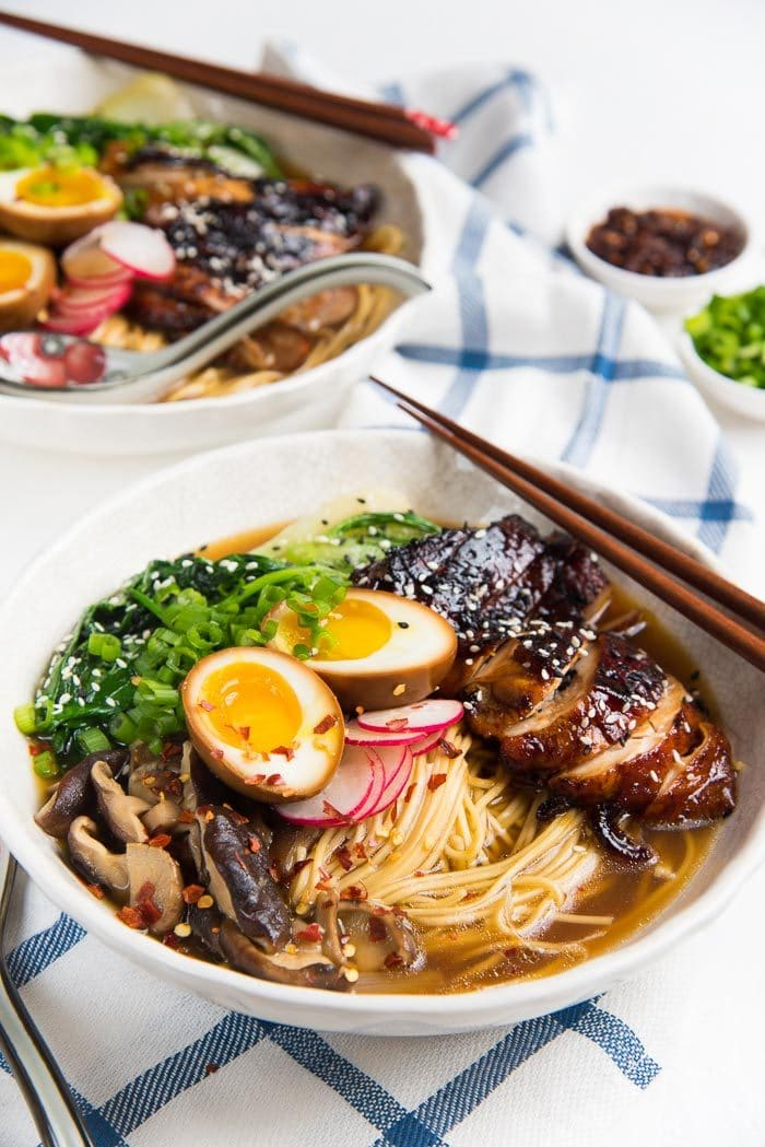 Easy Chicken ramen served in a wide white bowl, with caramelized soy chicken, ramen eggs and other toppings.