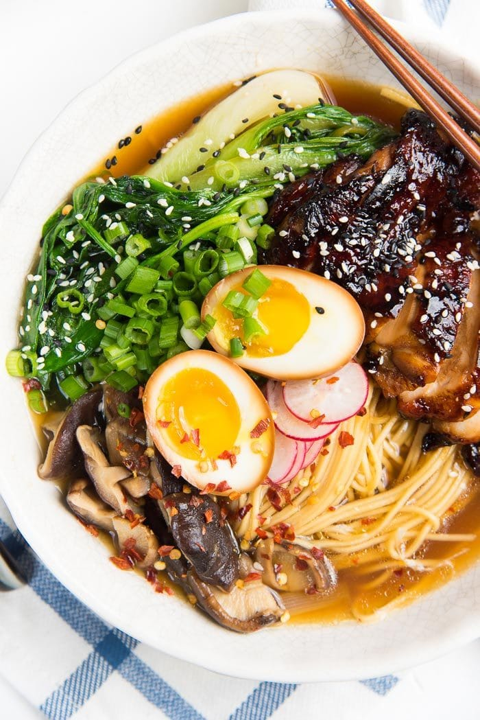 An overhead view of Easy chicken ramen, showing the ramen noodles, ramen egg, grilled chicken, greens, mushrooms and radishes.