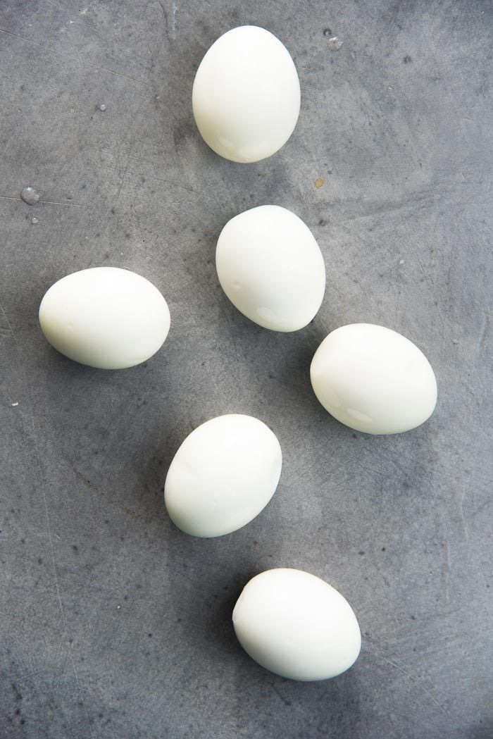 Soft boiled eggs places on a grey table top