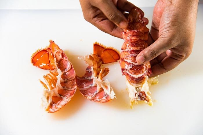 The two lobster tail shell cracked into two, with the lobster tail meat intact next to it.