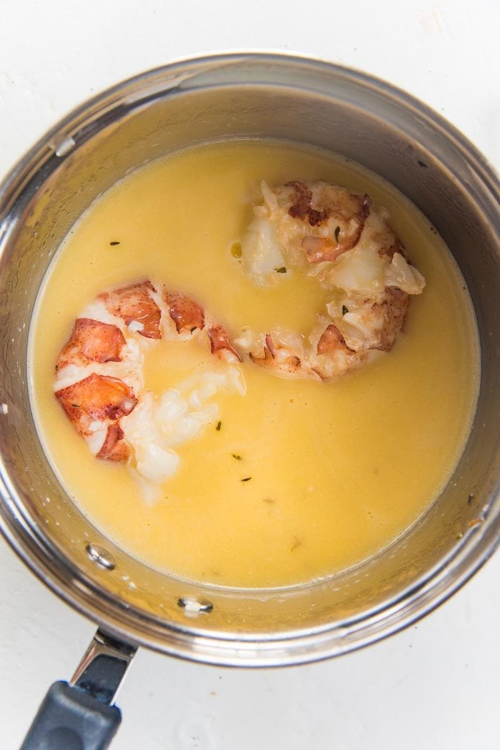 Lobster tails being poached in butter, in a small saucepan.