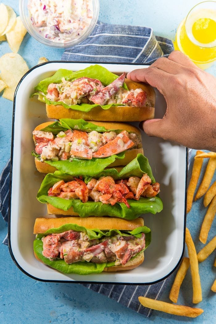 Four lobster rolls, Maine lobster rolls and Connecticut lobster rolls in a white tray