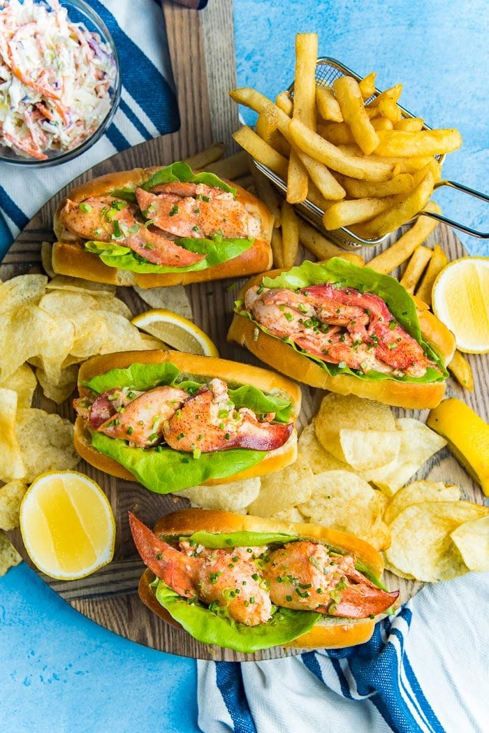 An overhead view of Maine lobster rolls on a wooden serving board with potato chips and french fries