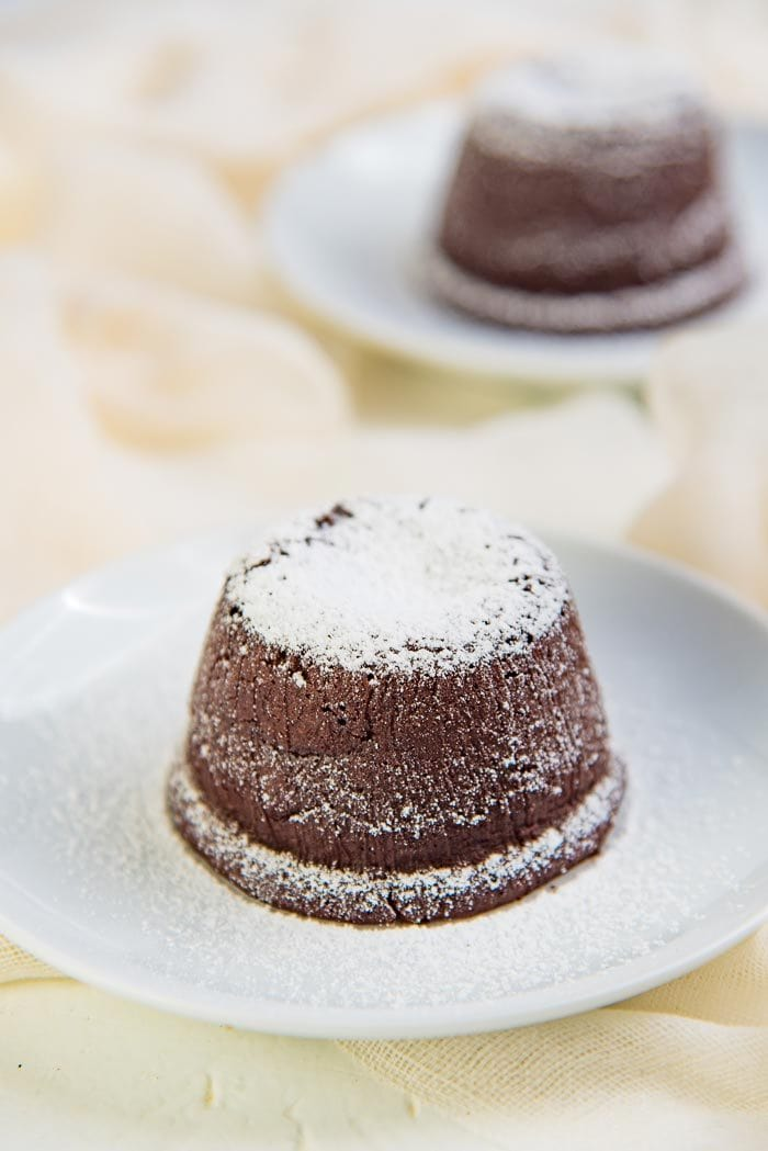 Chocolate molten lava cakes dusted with confectioner's sugar on a white serving plate