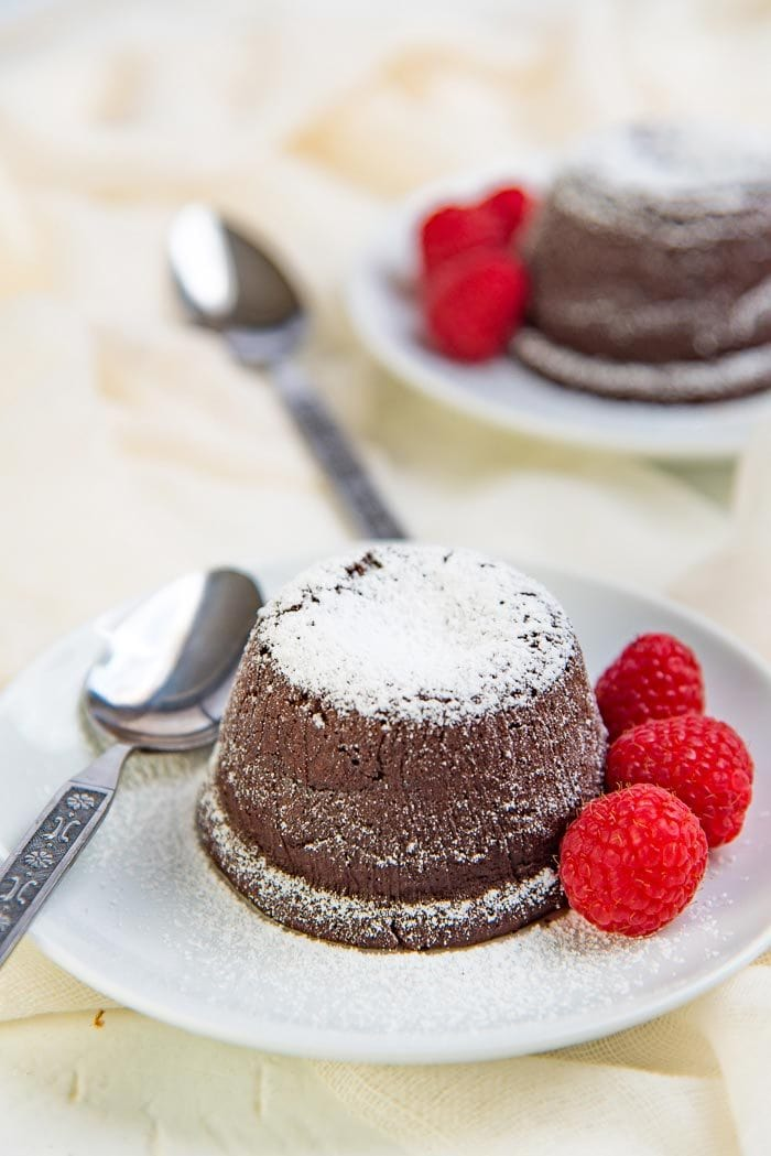 Chocolate molten cake on a white plate with raspberries, and another cake in the background.