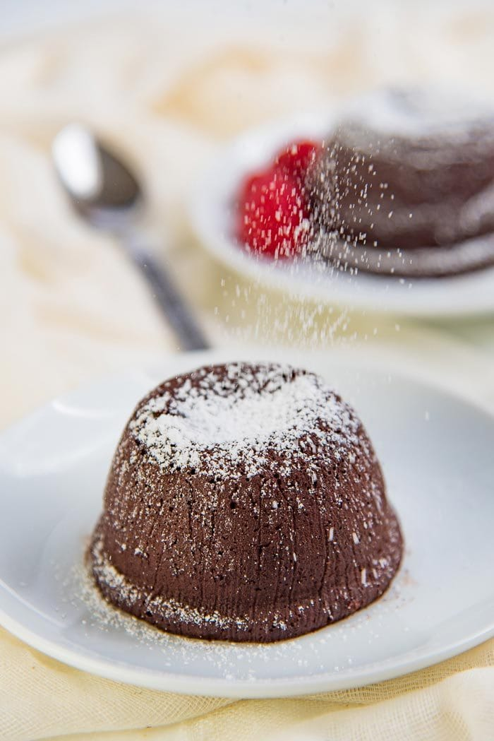 Chocolate molten lava cake being dusted with confectioner's dust.